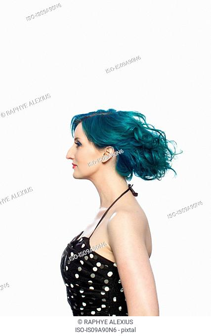 Young woman with green hair in profile against white background