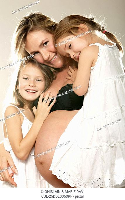 Pregnant woman with her two daughters