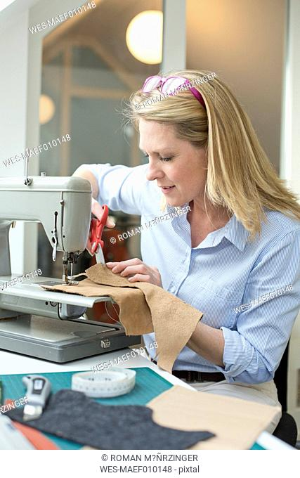 Woman with sewing machine tailoring