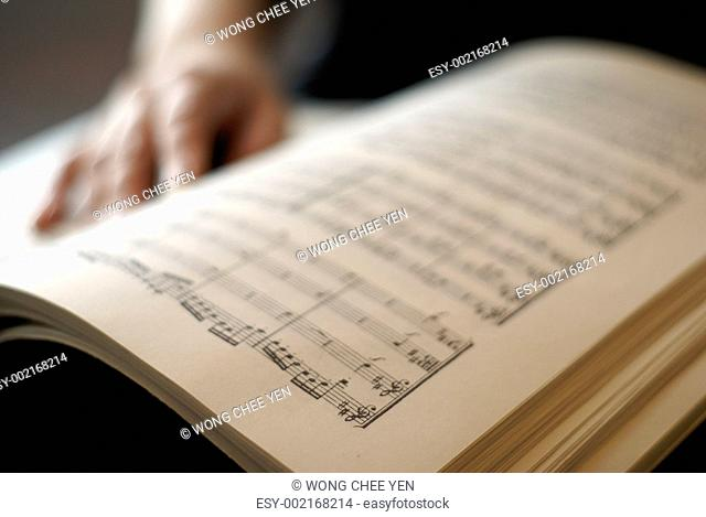 Female hand on musical score book page