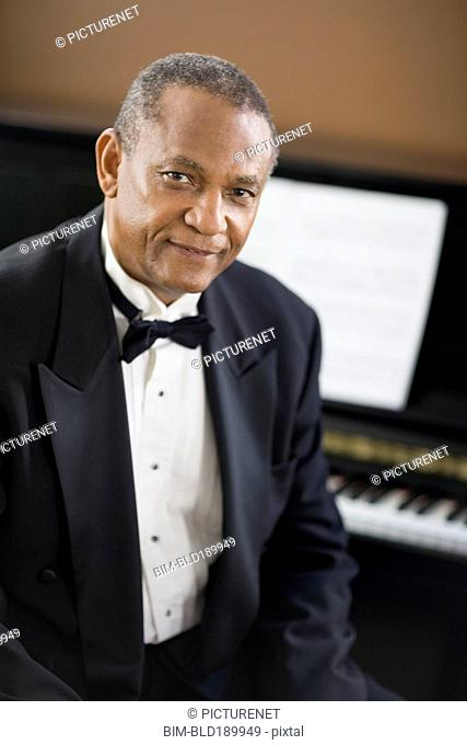 African man in tuxedo sitting in front of piano