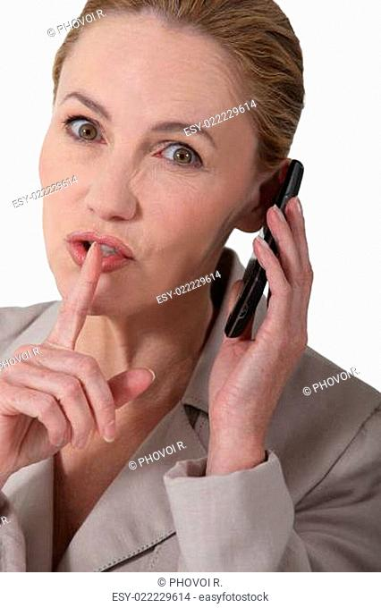 Woman indicating quiet whilst holding a phone