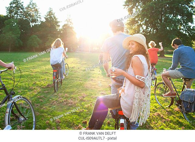 Rear view of party going adults in park on bicycles at sunset
