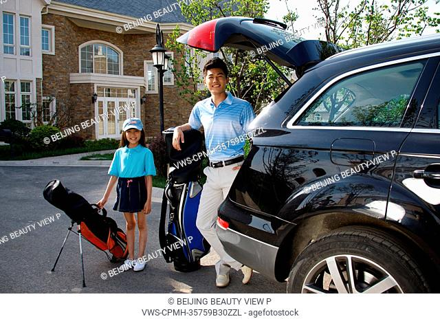 Oriental father and daughter standing by car in front of villa