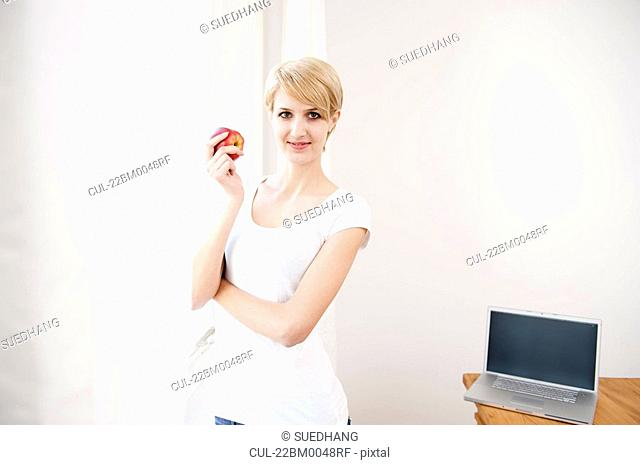 Woman with laptop and eating an apple
