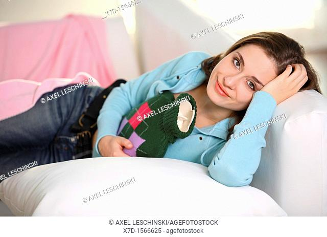 woman lies with hot water bottle on sofa