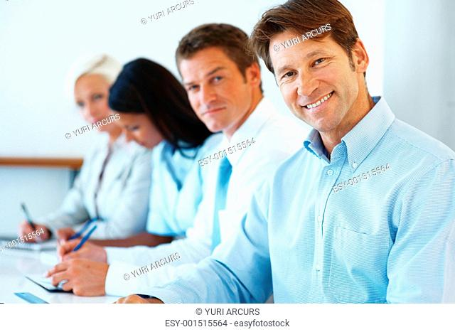 Portrait of successful young businessman attending business meeting with his colleagues at office
