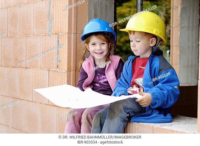 Two little children, siblings, wearing hard hats studying a building plan while planning their rooms at a house construction site
