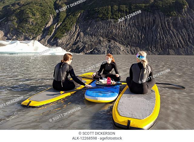 Three women sitting on top of their inflatable stand up paddle boards eating a snack in front of the Grewingk glacier in Kachemak Bay State Park