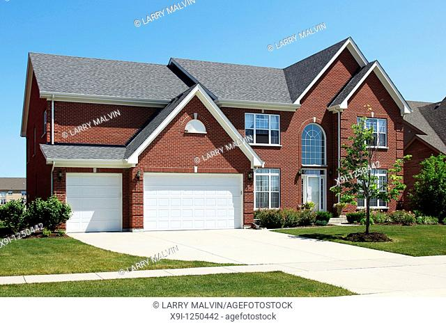 Red brick home in suburbs with three car garage