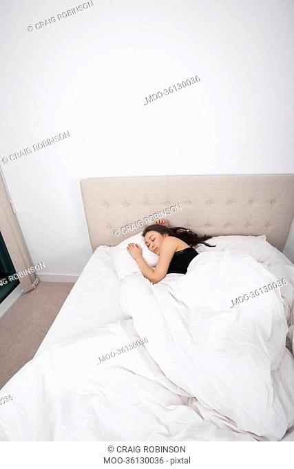 High angle view of young woman sleeping in bed