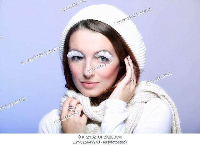 winter fashion beautiful woman in warm clothing stylish creative make up false eye lashes long white blue background