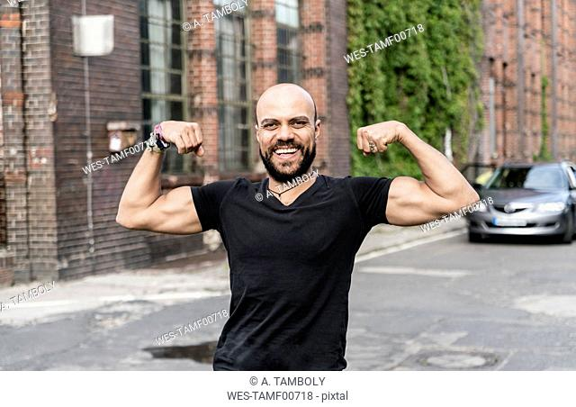 Portrait of smiling man flexing muscles