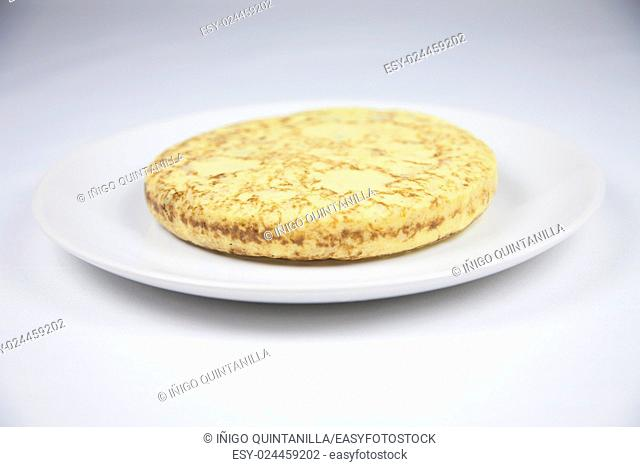 white dish with yellow spanish potato omelette on grey tablecloth