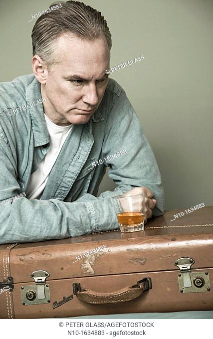 Middle-age man with a drink setting on a suitcase