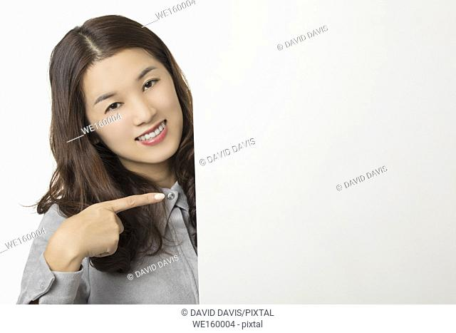 Beautiful Asian woman displaying a bit of attitude while holding a blank card isolated on a white background
