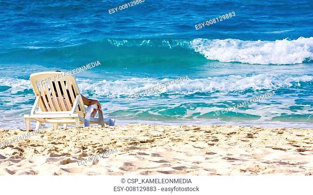 Woman sunbathing in a plastic chair on a beautiful beach in Cuba