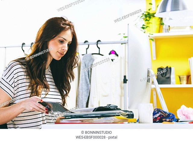 Portrait of female fashion blogger with magazine at her office