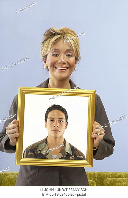 Proud mother holding picture of son