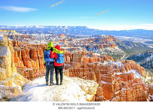 Tourists with views of the amphitheatre, bizarre snow-covered rocky landscape with Hoodoos in winter, Rim Trail, Bryce Canyon National Park, Utah, USA