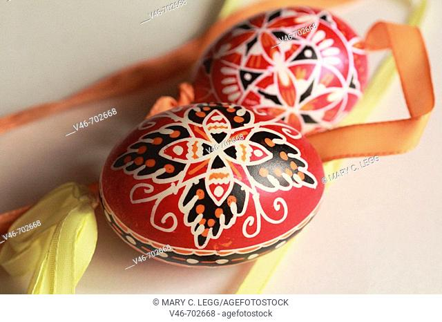 Two traditional handpainted red Czech Easter eggs with yellow and orange ribbons on a white background. The eggs are handcrafted traditional art of the Czech...