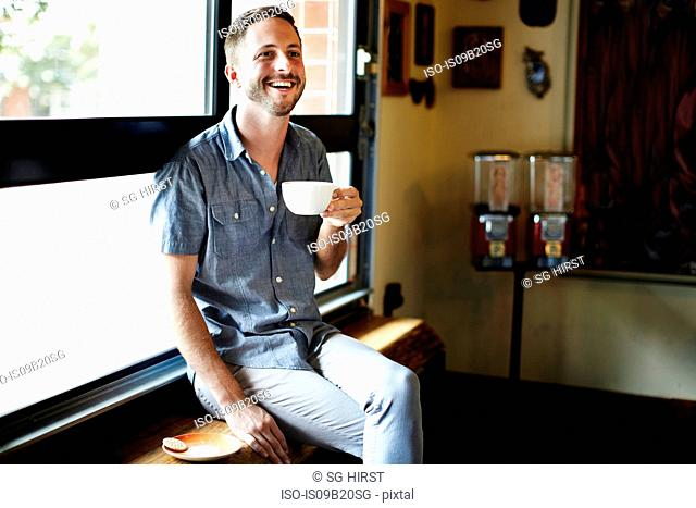 Young man sitting on cafe window seat drinking cappuccino