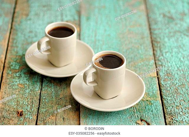 Two cups of coffee on old wooden table closeup