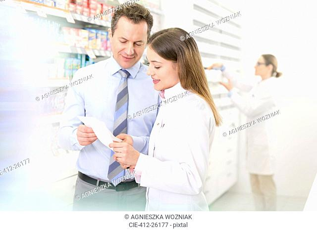Pharmacist and customer reviewing prescription in pharmacy