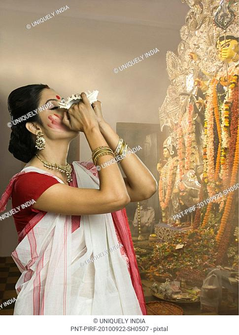 Woman blowing conch shell at Durga puja