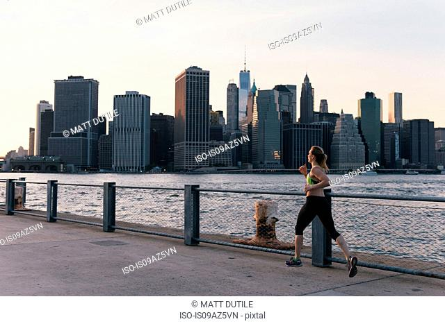 Young woman exercising outdoors,running along waterfront, Brooklyn, New York, USA