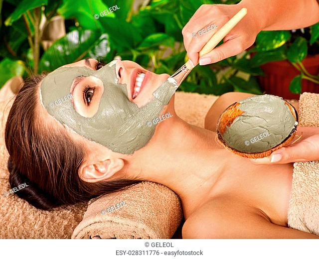 Woman with clay facial mask in beauty spa.Towel under the neck