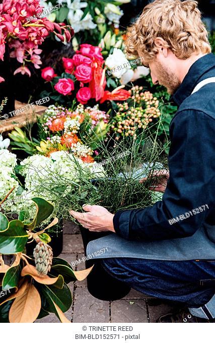 Caucasian florist arranging flowers outside shop