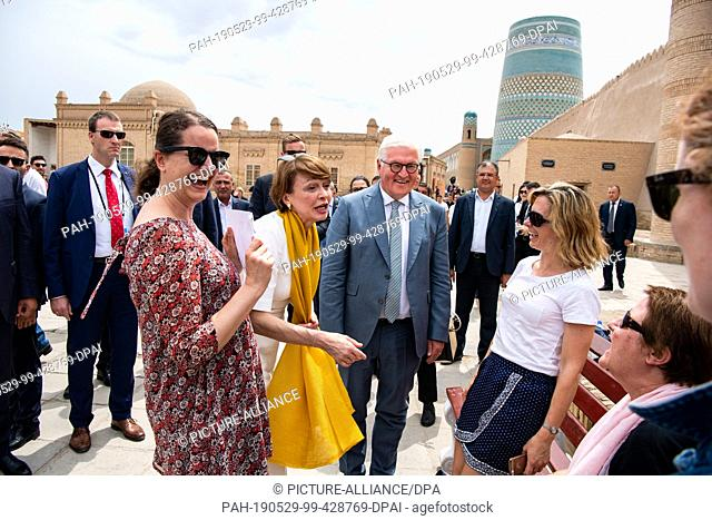 29 May 2019, Uzbekistan, Chiwa: Federal President Frank-Walter Steinmeier and his wife Elke Büdenbender talk to German tourists in the old town of Khiva