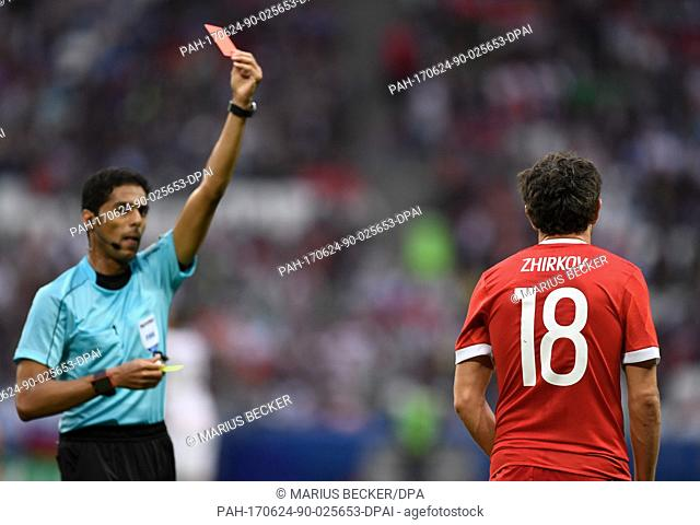 Referee Fahad al-Mirdasi (L) from Saudi Arabia shows Russia's Yuri Shirkov a red card during the group stage match pitting Mexico against Russia at the Kazan...