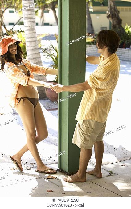 Young Hispanic couple playing around pole