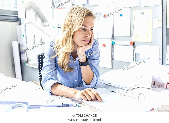 Pensive woman sitting at desk in office surrounded by paperwork