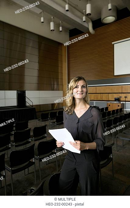 Portrait smiling woman with paperwork in auditorium