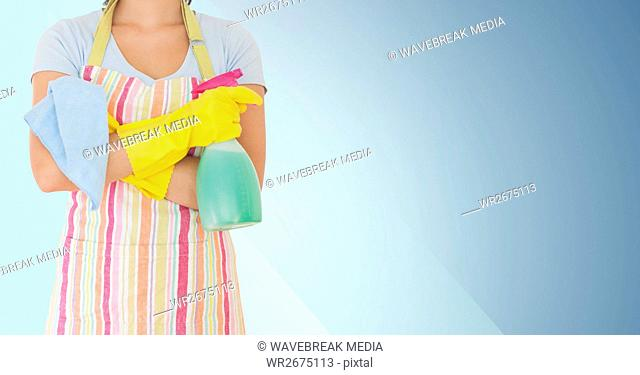 Mid section of woman holding spray bottle and napkin