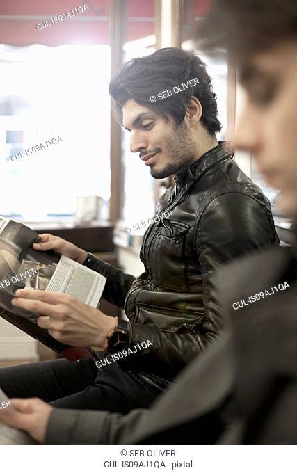 Man waiting in barbershop reading newspaper