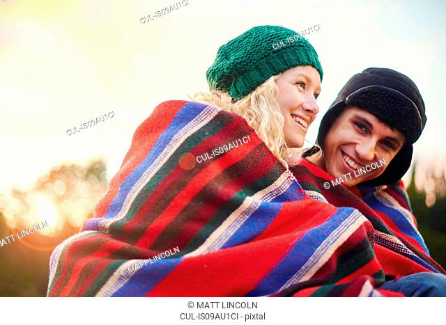 Portrait of romantic young camping couple wrapped in blanket