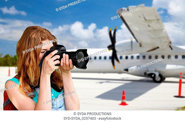 tourist woman photographing by camera over plane