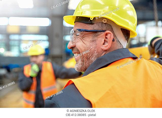 Profile smiling male worker in factory