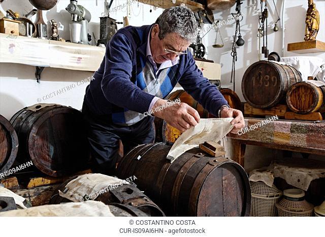 Man making and taking care over Aceto Balsamico Tradizionale di Modena