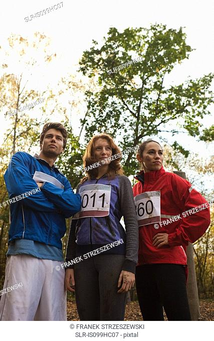 Young friends in sportswear standing together in forest