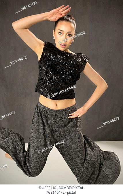 Attractive young woman dancing full length chopped, in elegant but edgy style in studio shot on gray background