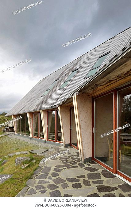Preikestolen Mountain Lodge, Strand, Norway. Architect Helen & Hard, 2008. South elevation, with windows of restaurant, against stormy sky