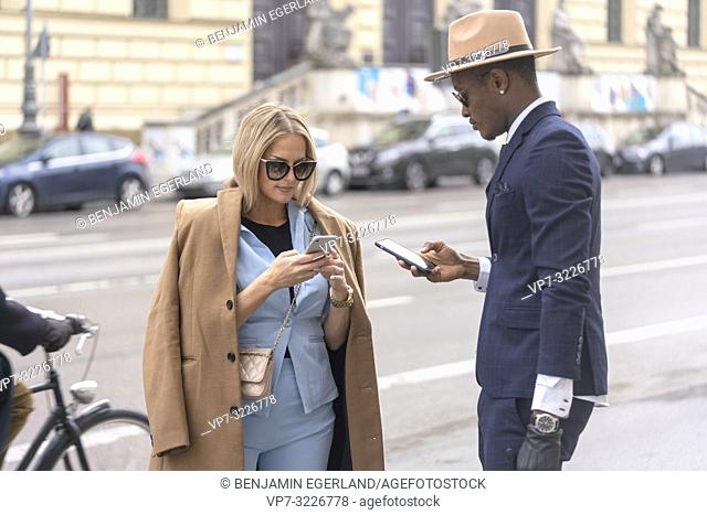 Fashionable couple with their smartphones on the street, in Munich, Germany
