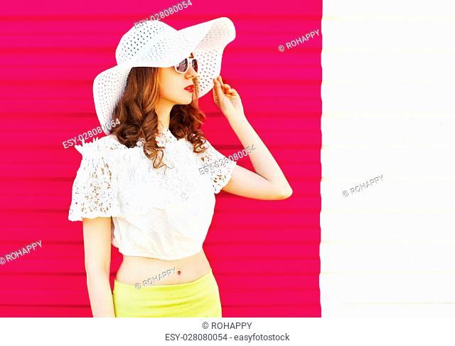 Woman in white summer straw hat looking over colorful pink background profile view