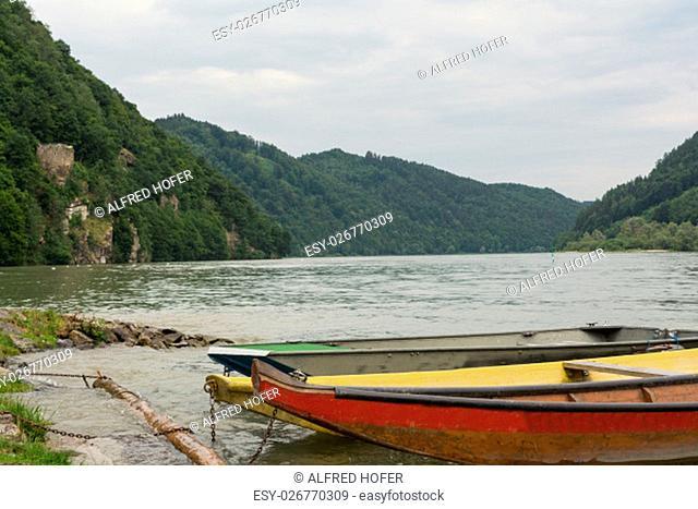 drei Holzboote haben am Donauufer angelegt