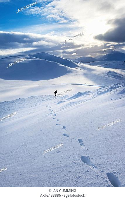 Walker on snowy, winter walk descending Creag Pitridh, near Laggan; Scotland